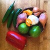 Fresh ingredients, peppers, garlic, limes and shallots in bowl on cutting board