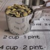 Measuring cups filled with pumpkin seeds